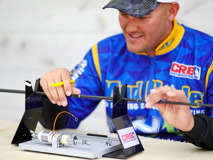 Blake Smith wraps the first guide on his new MHX custom fishing rod.